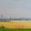 Prairie landscape with pasture land, golden fields with hazy images of Calgary Alberta skyline, including Calgary Tower silhouetting the pale blue sky.