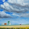 Prairie landscape with grain fields in foreground, big prairie sky with clouds, and an elevator and some farming type buildings on the horizon